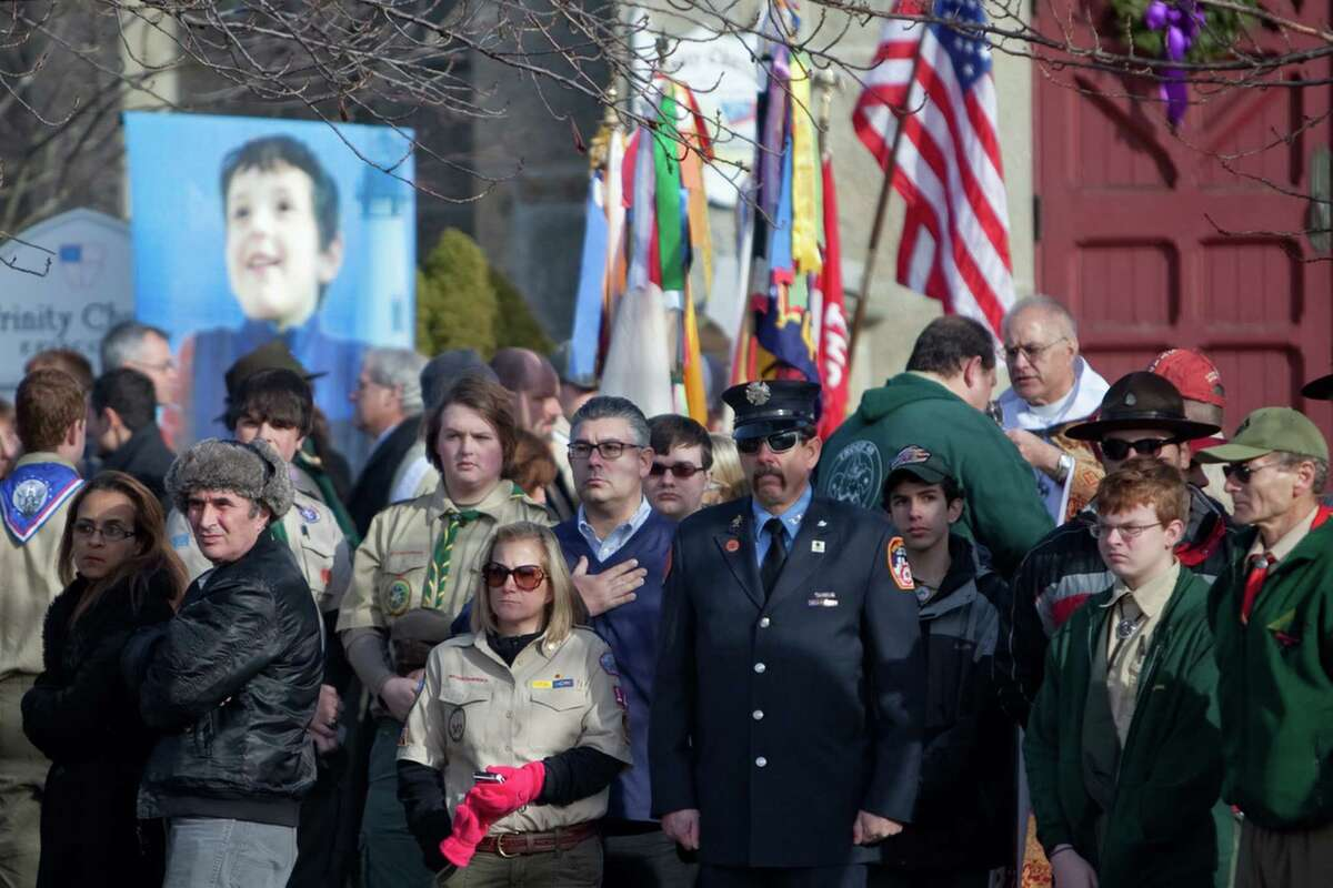 Mourners watch and stand at attention as a hearse from another funeral drives past the funeral for six year-old Benjamin Andrew Wheeler at Trinity Episcopal Church in Newtown on Thursday, December 20, 2012.