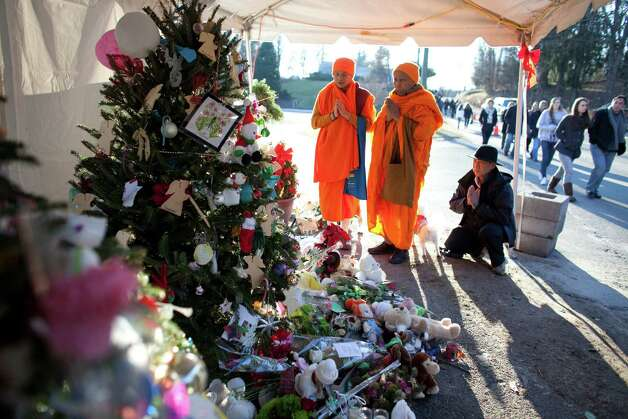 Buddhist monks Shaw Karnsomtob, left, and Choke Smornrit pray along with Eddie Wongvravit at a growing memorial near the entrance to Sandy Hook Elementary School, nine days after 20 students and 6 teachers were killed at the school by a gunman. The Buddhists traveled from Mount Vernon, New York to offer the prayer. The memorial site is becoming a pilgrimage of sorts as it draws mourners from around the country. Photo: JOSHUA TRUJILLO / HEARST NEWSPAPERS