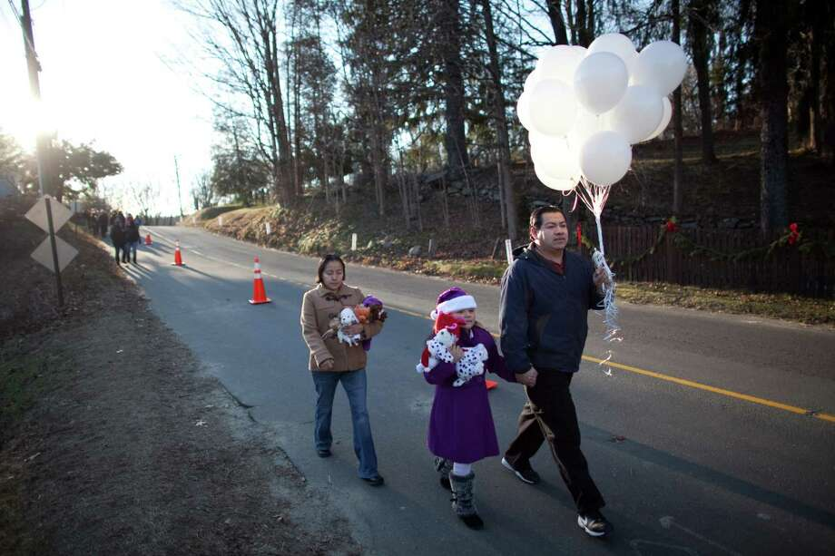 Mourners, including Leonardo Ortiz of West Haven, his daughter Sitlalli Ortiz and Olivia Lugo, walk up Riverside Road in what is becoming a pilgrimage for many to Sandy Hook Elementary School on Sunday, December 23, 2012, nine days after 20 students and 6 teachers were killed at the school by a gunman. Photo: JOSHUA TRUJILLO / HEARST NEWSPAPERS