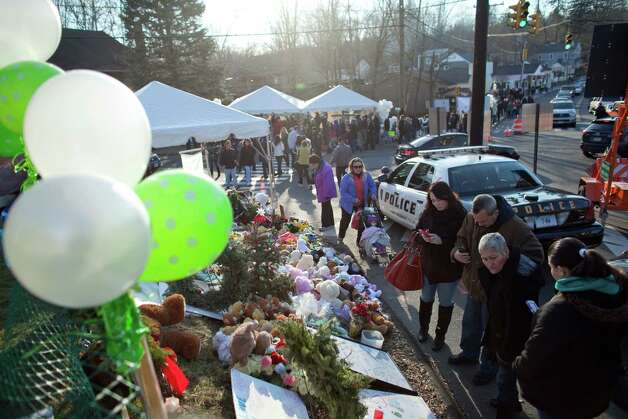 Large crowds gather at a growing memorial in Sandy Hook. The memorial site is becoming a pilgrimage of sorts as it draws mourners from around the country. Photo: JOSHUA TRUJILLO / HEARST NEWSPAPERS