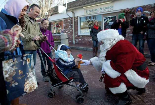 Santa Claus stops to say hi to Austin Rotonto, 6, of Stratford, and his family while visiting with children in Sandy Hook on Sunday, December 23, 2012, nine days after 28 people were killed during a day of horrific violence in Newtown. Photo: JOSHUA TRUJILLO / HEARST NEWSPAPERS