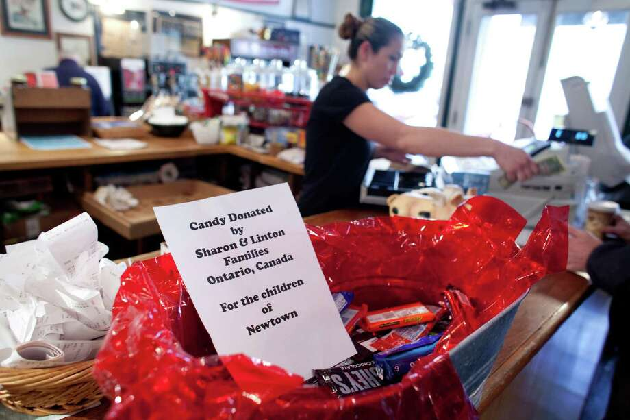 A sign at the Newtown General Store offers candy for the children of Newtown on Saturday, December 22, 2012. Another sign in the business said all hot drinks were paid for by a donor from New York. The outpouring of support and gifts from around the world has been appreciated by thankful residents. Photo: JOSHUA TRUJILLO / HEARST NEWSPAPERS