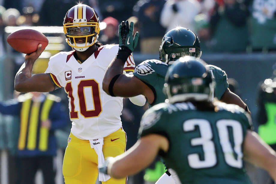 Washington Redskins quarterback Robert Griffin III, left, passes under pressure from Philadelphia Eagles' Brandon Graham, center, and Colt Anderson in the first half of an NFL football game, Sunday, Dec. 23, 2012, in Philadelphia. (AP Photo/Mel Evans) Photo: Mel Evans