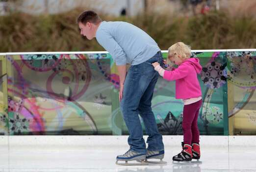 Anoton Gerbrandy left, pulls his five-year-old daughter Helena Gerbrandy while ice skating at Discovery Green Sunday, Dec. 23, 2012, in Houston. The ICE at Discovery Green will be open daily through January 27, 2013. Photo: James Nielsen, Chronicle / © Houston Chronicle 2012