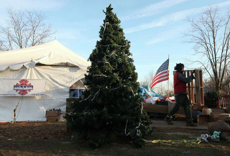 NEW YORK, NY - DECEMBER 23:  A man carries a pallet past a Christmas tree outside a distribution relief tent for those affected by Superstorm Sandy on December 23, 2012 in the Staten Island borough of New York City. Staten Island was hit hard by Sandy and some homes and businesses remain without power. Photo: Mario Tama, Getty Images / 2012 Getty Images