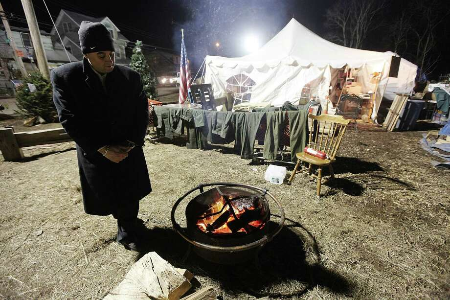 NEW YORK, NY - DECEMBER 23:  A resident who did not want to be identified, whose home was damaged by Superstorm Sandy, keeps warm by a fire outside a distribution relief tent for those affected by the storm on December 23, 2012 in the Staten Island borough of New York City. Staten Island was hit hard by Sandy and some homes and businesses remain without power. Photo: Mario Tama, Getty Images / 2012 Getty Images