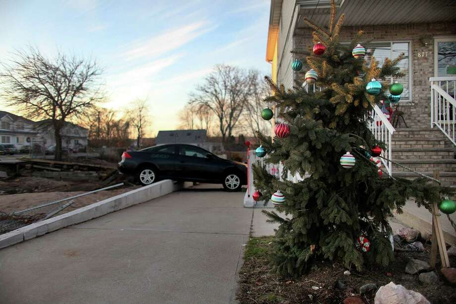 NEW YORK, NY - DECEMBER 23:  A Christmas tree stands next to property and a vehicle damaged by Superstorm Sandy on December 23, 2012 in the Staten Island borough of New York City. Staten Island was hit hard by Sandy and some homes and businesses remain without power. Photo: Mario Tama, Getty Images / 2012 Getty Images