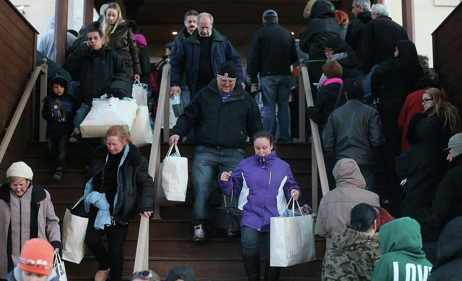 NEW YORK, NY - DECEMBER 23:  People carry away bags of free items as others wait to enter at a pop-up shopping event organized by Fashion Delivers for victims of Hurricane Sandy on December 23, 2012 in the Staten Island borough of New York City. The two-day event was expected to draw 1,000 people to holiday shop for free unused donated apparel. Staten Island was hit hard by Hurricane Sandy. Photo: Mario Tama, Getty Images / 2012 Getty Images