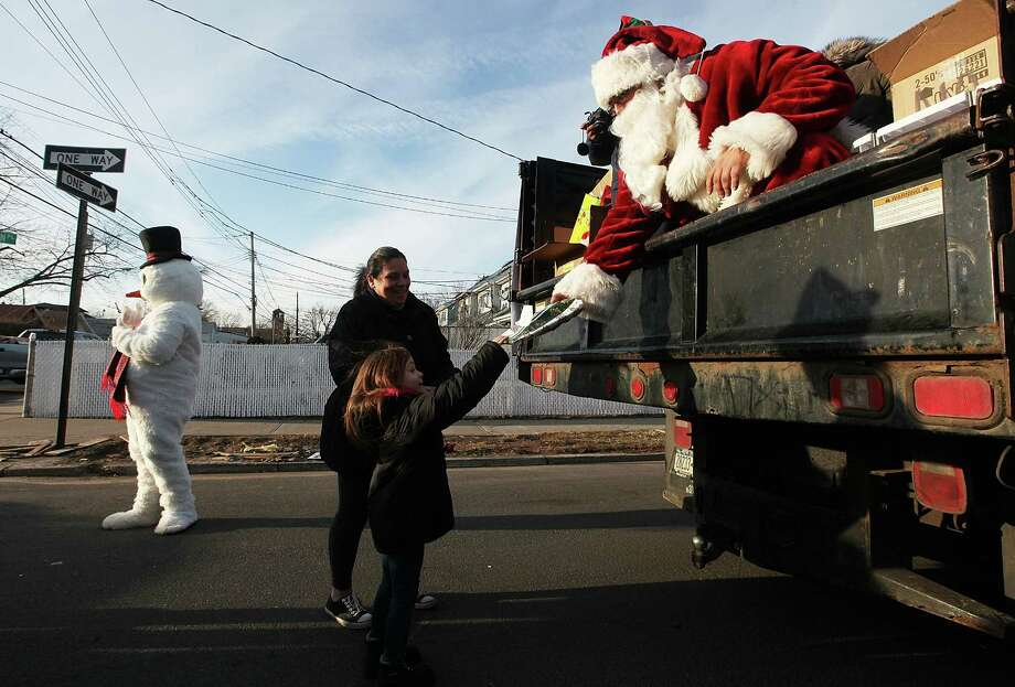 NEW YORK, NY - DECEMBER 23: Mike 'Loco' Hoffman, aka Santa Claus, passes out free gifts from the back of a truck to Gloria Lullo and her granddaughter Jolee in the Midland Beach neighborhood which was heavily damaged by Superstorm Sandy on December 23, 2012 in the Staten Island borough of New York City. Staten Island was hit hard by Sandy and some homes and businesses remain without power. Photo: Mario Tama, Getty Images / 2012 Getty Images