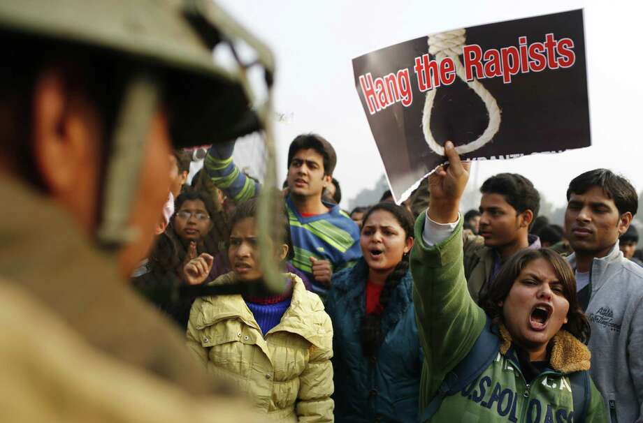 An Indian demonstrator (2nd R) shouts slogans at the police during a protest calling for  better safety for women following the rape of a student last week, in front the India Gate monument in New Delhi on December 23, 2012. In the biggest protest so far, several thousand college students rallied at the India Gate monument in the heart of the capital where they were baton-charged, water cannoned and tear gassed by the police.    TOPSHOTS AFP PHOTO/ Andrew Caballero-ReynoldsAndrew Caballero-Reynolds/AFP/Getty Images Photo: ANDREW CABALLERO-REYNOLDS, AFP/Getty Images / PRO AFP