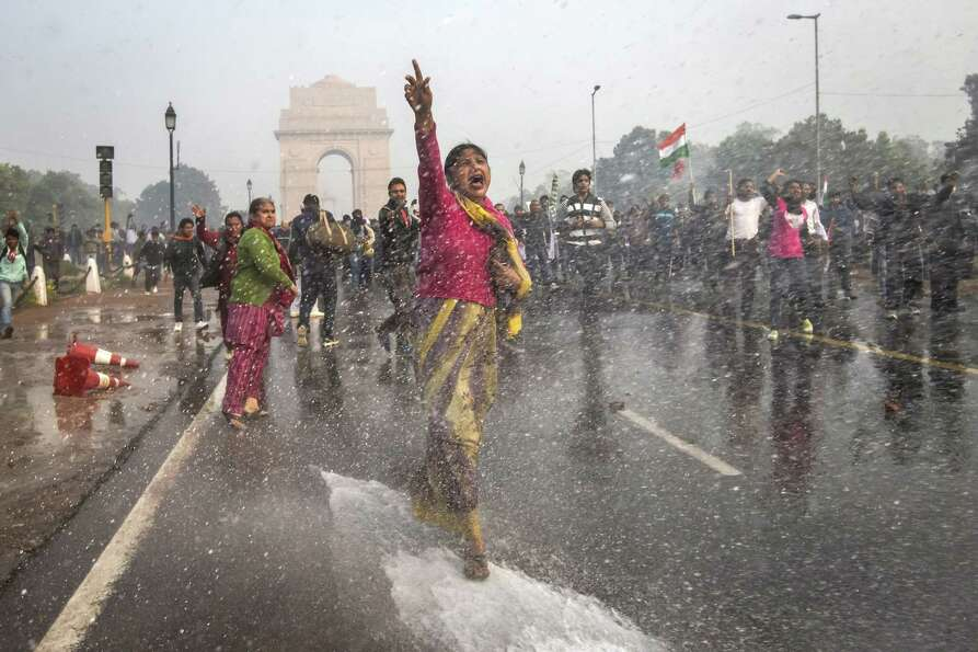 NEW DELHI, INDIA - DECEMBER 23: A protestors chants slogans as she braces herself against the spray