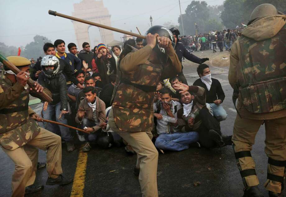 Protesters shield themselves as Indian police prepare to beat them with sticks during a violent demonstration near the India Gate against a gang rape and brutal beating of a 23-year-old student on a bus last week, in New Delhi, India, Sunday, Dec. 23, 2012. The attack last Sunday has sparked days of protests across the country. Photo: Kevin Frayer, AP / AP