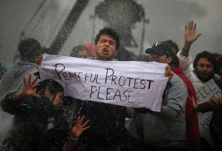 Protesters react as Indian police officers use a water cannon to disperse them near the India Gate a
