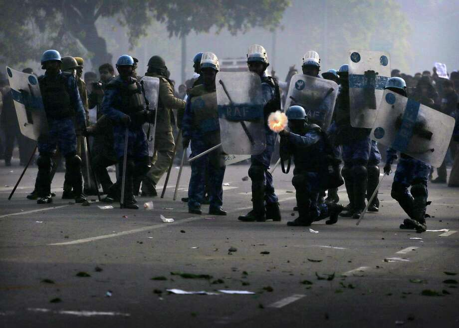 Indian police fire tear gas towards protesters, not seen, during a violent demonstration near the India Gate against a gang rape and brutal beating of a 23-year-old student on a bus last week, in New Delhi, India, Sunday, Dec. 23, 2012. The attack last Sunday has sparked days of protests across the country. Photo: Kevin Frayer, AP / AP