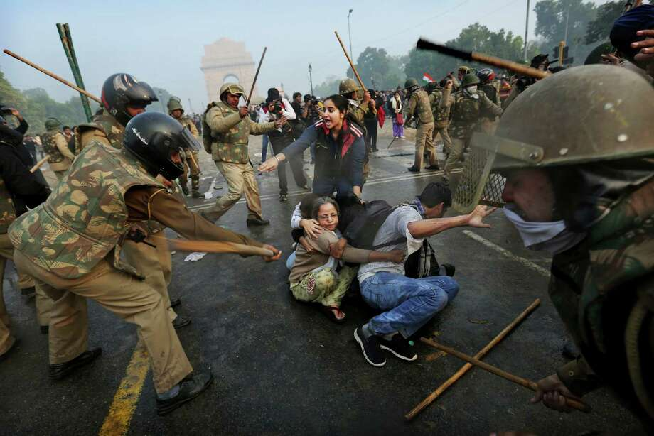 Protesters shield themselves as Indian police beat them with sticks during a violent demonstration near the India Gate against a gang rape and brutal beating of a 23-year-old student on a bus last week, in New Delhi, India, Sunday, Dec. 23, 2012. The attack last Sunday has sparked days of protests across the country. Photo: Kevin Frayer, AP / AP