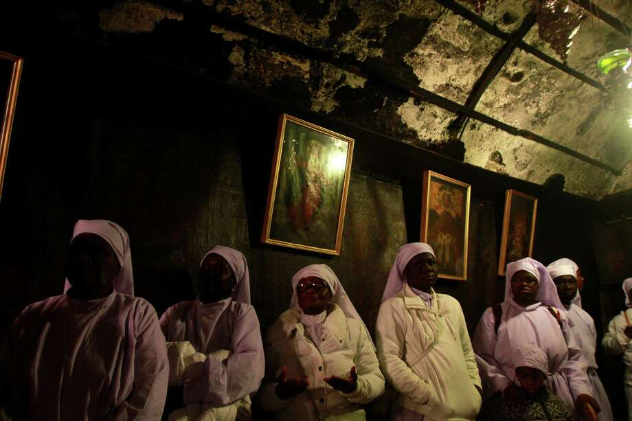 TOPSHOTS Nigerian Christian pilgrims pray inside the Grotto at the Church of the Nativity in the biblical West Bank city of Bethlehem, believed to be the birthplace of Jesus Christ, on December 24, 2012. Thousands of Palestinians and tourists were flocking to Bethlehem to mark Christmas at the site where many believe Jesus Christ was born. AFP PHOTO/MUSA AL-SHAERMUSA AL-SHAER/AFP/Getty Images Photo: MUSA AL-SHAER, AFP/Getty Images / AFP PHOTO/MUSA AL SHAER