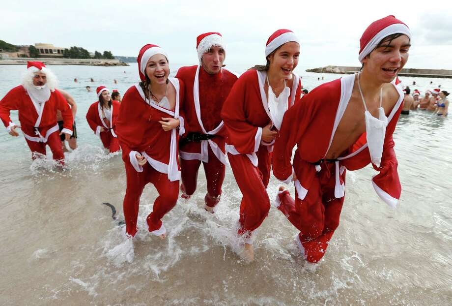 People dressed up as Santa Claus enjoy a traditional Christmas bath on December 23, 2012 in Monaco. TOPSHOTS  AFP PHOTO / VALERY HACHEVALERY HACHE/AFP/Getty Images Photo: VALERY HACHE, AFP/Getty Images / AFP