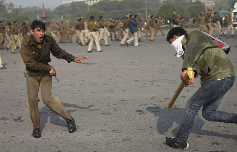 An Indian student tries to hit a policeman with an iron rod during a protest in New Delhi, India, Sa