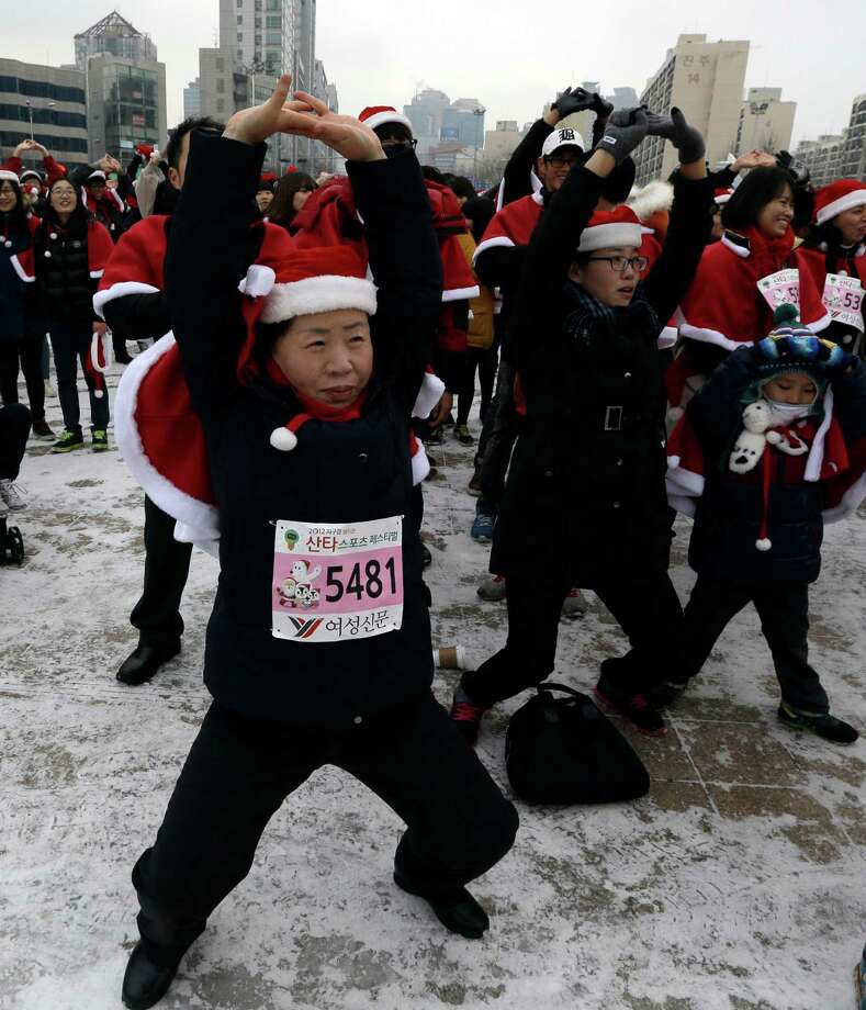 South Koreans wearing Santa Claus costumes exercise before taking part in the Santa Marathon race in Seoul, South Korea, Saturday, Dec. 22, 2012. More than 1,000 people participated in the 5-kilometer (3.1 miles) charity run to raise money for young athletes who play unpopular sports on the occasion of Christmas which is one of the biggest holidays in South Korea. Photo: Lee Jin-man, AP / AP