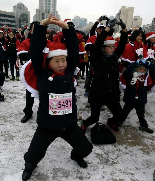South Koreans wearing Santa Claus costumes exercise before taking part in the Santa Marathon race in