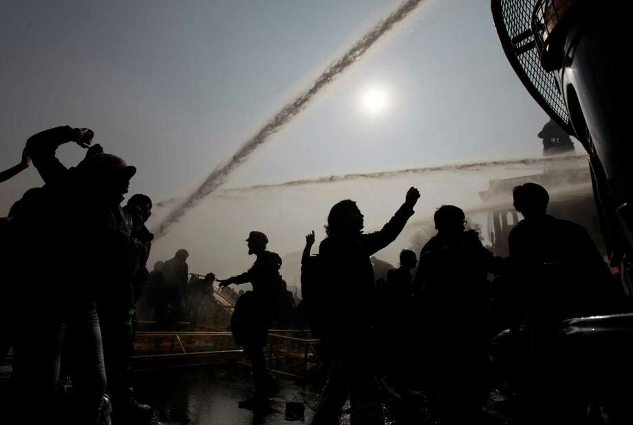 Indian protesters shout slogans as they break a police barricade after policemen used water cannon to disperse them during a protest in New Delhi, India, Saturday, Dec. 22, 2012. Police in India's capital used tear gas and water cannons Saturday to push back thousands of people who tried to march to the presidential mansion to protest the recent gang rape and brutal beating of a 23-year-old student on a moving bus. Photo: Altaf Qadri, AP / AP