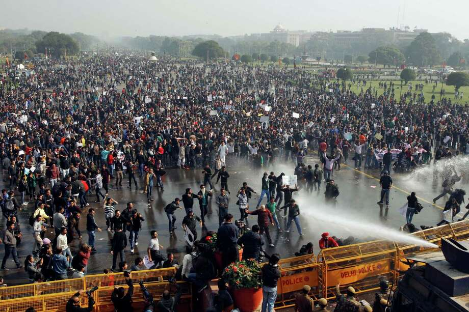 Indian protesters shout slogans as policemen use water cannon to disperse them during a march towards the Presidential Palace in New Delhi, India, Saturday, Dec. 22, 2012. Police used tear gas and water cannons to push back thousands of people who tried to march to the presidential mansion to protest the recent gang rape and brutal beating of a 23-year-old student on a moving bus. Photo: Tsering Topgyal, AP / AP