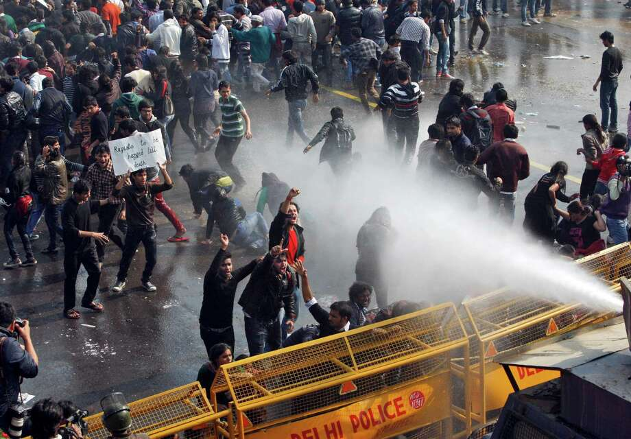 Indian people shout slogans as policemen use water canon to disperse them during a protest in New Delhi, India, Saturday, Dec. 22, 2012. Police used tear gas and water cannons to push back thousands of people who tried to march to the presidential mansion to protest the recent gang rape and brutal beating of a 23-year-old student on a moving bus. Photo: Tsering Topgyal, AP / AP