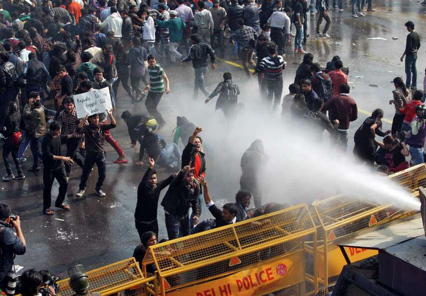 Indian people shout slogans as policemen use water canon to disperse them during a protest in New De
