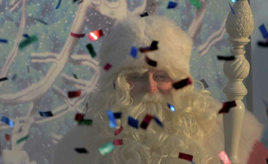 An actor dressed as Ded Moroz (Grandfather Frost), the Russian Santa Claus, smiles through smoke from a fire cracker and flying confetti during a welcome ceremony for him in Moscow's Gorky Park, on December 24, 2012. New Year's is the biggest holiday of the year in Russia, and is followed by the Orthodox Christmas on January 7. AFP PHOTO / KIRILL KUDRYAVTSEVKIRILL KUDRYAVTSEV/AFP/Getty Images Photo: KIRILL KUDRYAVTSEV, AFP/Getty Images / AFP