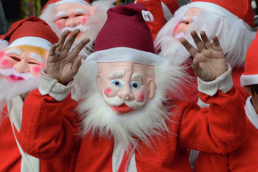 Indian schoolchildren dressed as Santa Claus ride on a cycle-rickshaw through a street in Amritsar o