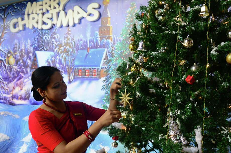 A Bangladeshi woman decorates a tree in Dhaka on Christmas Eve, December 24, 2012. Bangladeshi Christians make up only 0.08 percent of the population of the predominatly Muslim nation. AFP PHOTO/ Munir uz ZAMANMUNIR UZ ZAMAN/AFP/Getty Images Photo: MUNIR UZ ZAMAN, AFP/Getty Images / AFP
