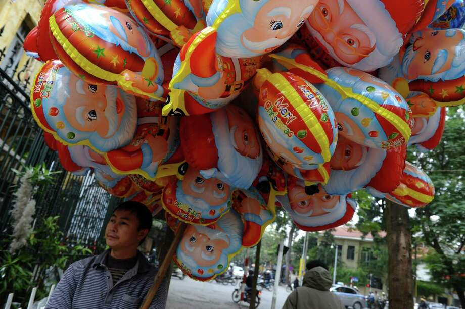 A vendor stands selling Santa Claus balloons outside a church in downtown Hanoi on December 24, 2012. Churches, shops, restaurants and shopping mails are being decorated in the Southeast Asian communist nation where some 6 million catholic community are preparing to celebrate Christmas. AFP PHOTO/HOANG DINH NamHOANG DINH NAM/AFP/Getty Images Photo: HOANG DINH NAM, AFP/Getty Images / AFP