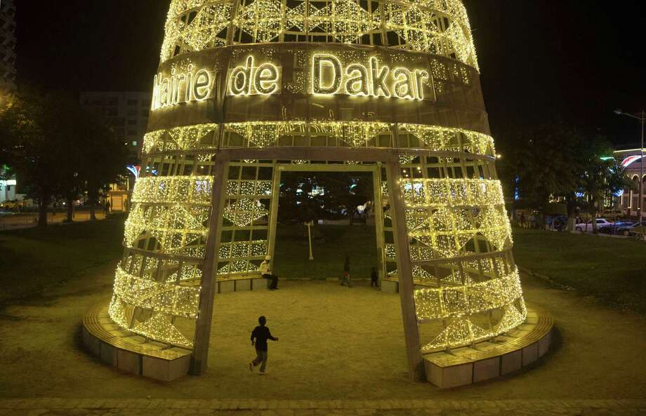 "In this Wednesday, Dec. 12, 2012 photo, a child runs through a giant cone of lights, reading ""Mayor of Dakar,"" in central Dakar, Senegal. As Christmas approaches in mostly Muslim Senegal, vendors ply the streets selling tinsel, artificial trees, and inflatable Santas, and the main boulevards are all aglow in holiday lights. Senegal, a moderate country along Africa's western coast, has long been a place where Christians and Muslims coexist peacefully and share in each other's holidays. Photo: Rebecca Blackwell, AP / AP"