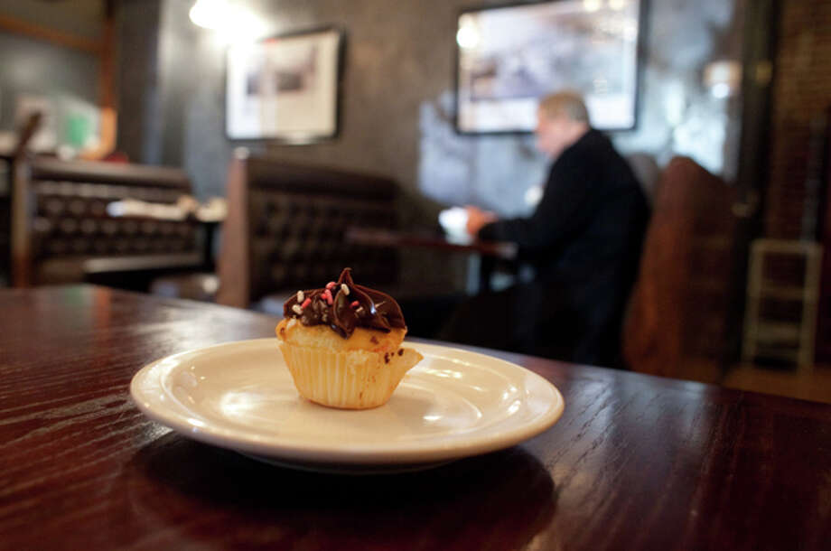 A cupcake sits on a table at the Stone River Grille after it was given to a customer on Friday, December 21, 2012. Earlier in the day the family of Grace McDonnell stopped by the restaurant and ordered cupcakes for all the customers that came into the restaurant that day. McDonnell, 7, one of the students killed at Sandy Hook Elementary, loved cupcakes. Photo: Joshua Trujillo/Hearst Newspapers
