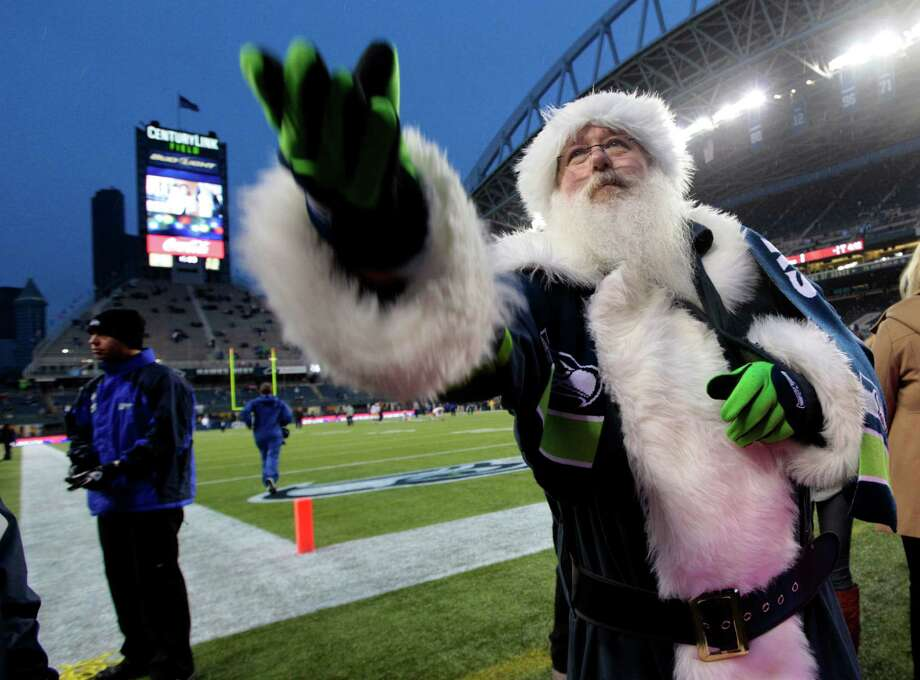 The Big Guy joined the Sea Gals. Neal Nilsen, of Federal Way, wore a Santa costume in team colors to throw candy to fans. Note to Santa: Get Russell Wilson to throw for you. Photo: Ap/getty