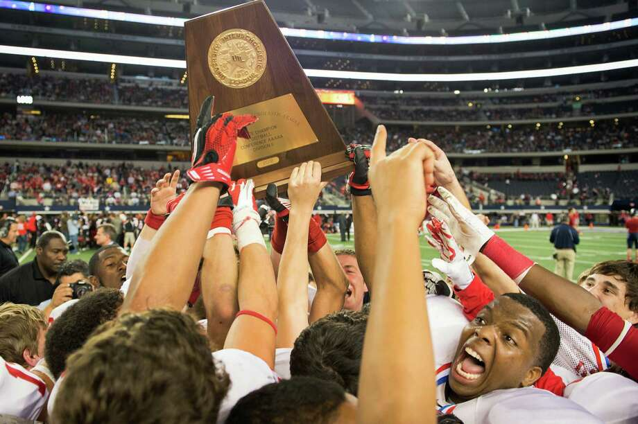 Katy players, including defensive lineman Nathan Adams, bottom right, celebrated with the state championship trophy after a 35-24 victory over Cedar Hill in the Class 5A Division II state championship football game in Arlington at Cowboys Stadium on Saturday. Photo: Smiley N. Pool, Staff / © 2012  Houston Chronicle