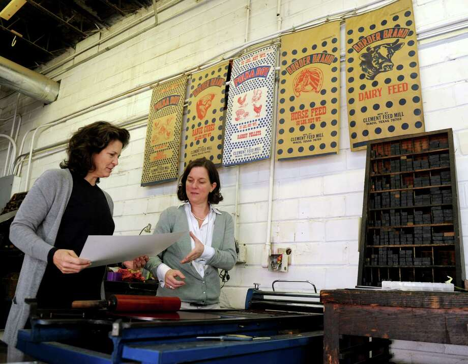 Madonna Badger and Kate Askew make a print on a press in Askew's shop, Yella Dog Press, in Little Rock, Arkansas, on Sunday, December 2, 2012. Photo: Lindsay Niegelberg / Stamford Advocate