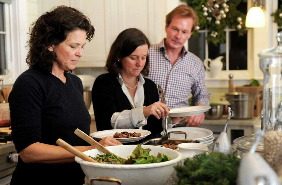 Madonna Badger stands with P. Allen Smith, center, and Kate Askew, right, as they have dinner in Smith's home in Little Rock, Arkansas, on Sunday, December 2, 2012. Photo: Lindsay Niegelberg / Stamford Advocate