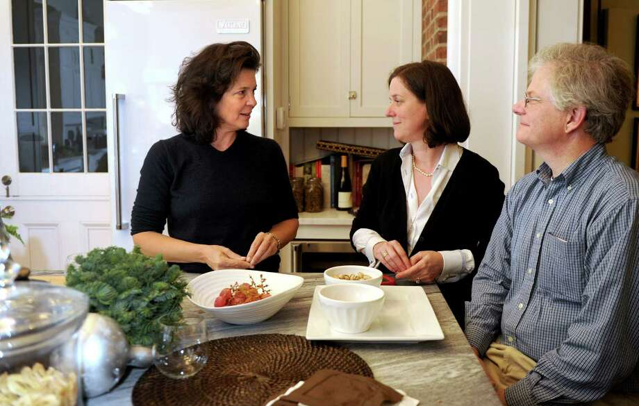 Madonna Badger, left, talks with Kate Askew, center, and Jess Askew, right, on Sunday, December 2, 2012, as they reminice about Badger's time living in Little Rock, Arkansas. Badger moved in with the Askew family after her three daughters and parents were killed in a Christmas day fire in her Shippan home in 2011. Photo: Lindsay Niegelberg / Stamford Advocate