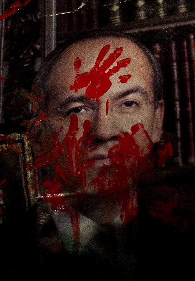 A photograph of Mexican President Felipe Calderon symbolically bloodstained by members of the Peace and Dignity Movement during a protest in farewell Mexican President Felipe Calderon who will leave the presidency next December 1 in Mexico City on November 28, 2012. More than 50,000 people have been killed after President Felipe Calderon launched a crackdown on the drug cartels in December 2006. AFP PHOTO/ Pedro PARDOPedro PARDO/AFP/Getty Images