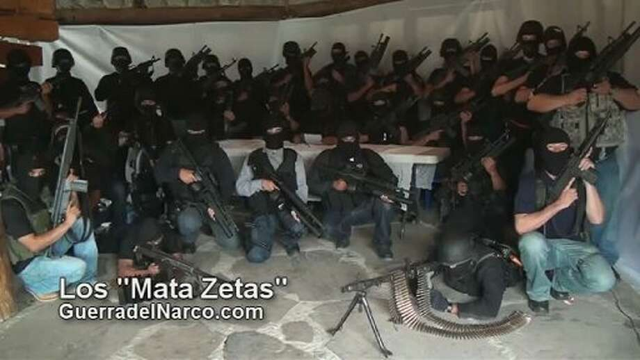 Screen capture of a paramilitary group which vowed to eliminate the Zetas, reputedly Mexico's most violent drug gang, in a video posted on the Internet on July 27, 2011 several days after 49 bodies were found on the streets of Veracruz. The video, according to its creators, shows a group of masked men, dressed in black and seated at a white table, calling themselves the Mata Zetas,  or Kill Zetas. Our intention is to let the people of Veracruz know that these dregs of society are not invincible,  one of them says after offering apologies to the public and the authorities. AFP PHOTO / - (Photo credit should read -/AFP/Getty Images)