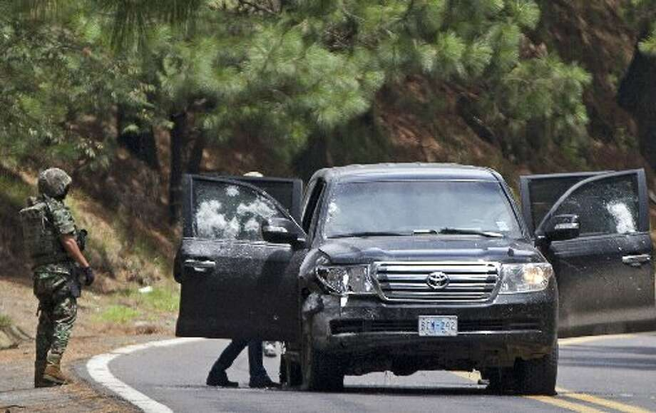 In this Aug. 24, 2012 file photo, Mexican military personnel check a vehicle in which two United States government employees were shot on the highway leading to the city of Cuernavaca, near Tres Marias, Mexico. Mexican prosecutors on Friday, Nov. 9, 2012, charged 14 federal police officers with trying to kill two CIA officers and a Mexican navy captain in the August ambush. (AP Photo/Alexandre Meneghini, File)