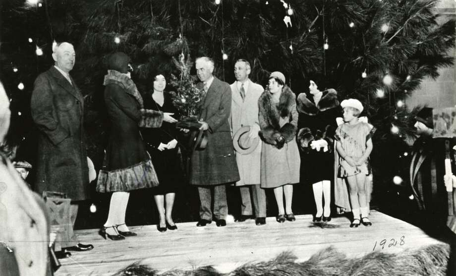 In 1924, the Tree of Light was outside the old City Hall which occupied what is now Old Market Square. The chairman of the 1928 debutantes presents Mayor Oscar Holcombe with a miniature Tree of Light. (Chronicle file)