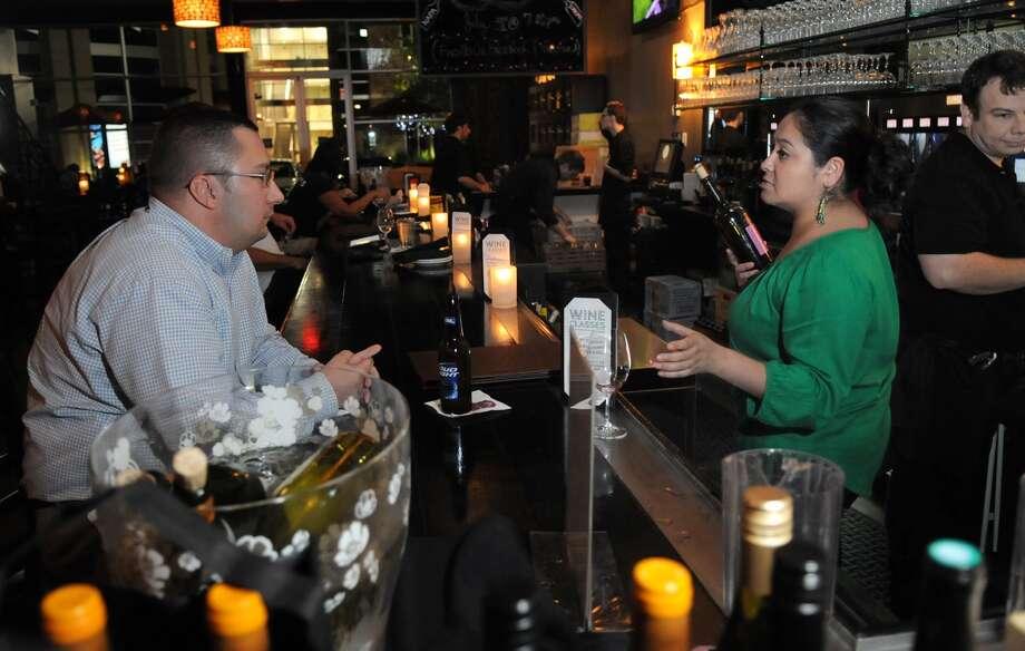 Brandon Lancaster of Kingwood talks wine with Yvette Perez of The Tasting Room at Kings Harbor. Photo: Jerry Baker, Freelance