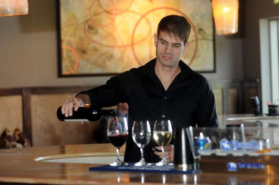 Bartender Brandon Dowell of Spring pours wine at the wine bar Crush, 20 Waterway Suite 200, The Woodlands. Photo: Jerry Baker, Freelance