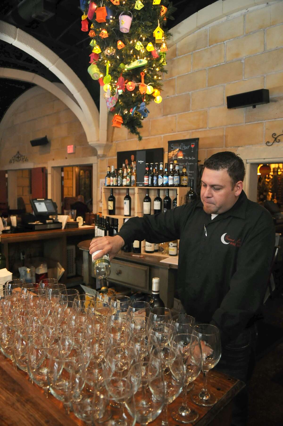 Manager Mike Cantu pours a glass of wine at the Crescent Moon Wine Bar and Restaurant in Spring.