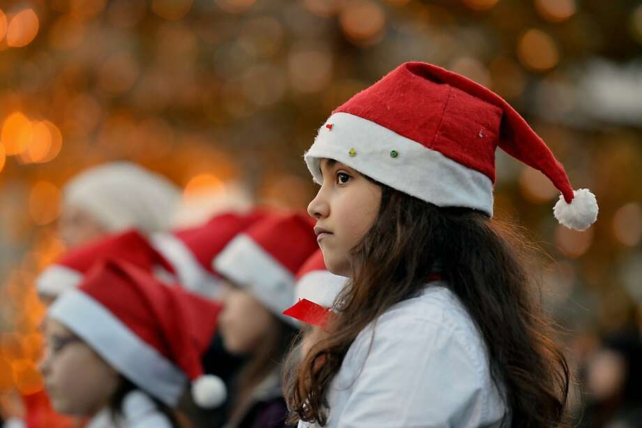 A young girl dressed as Santa Claus takes part in the unveiling ceremony of the crib in St Peter's Square in the Vatican, on December 24, 2012. Pope Benedict XVI will celebrate a late Christmas night holy mass at St. Peter's Basilica to mark the nativity of Jesus Christ. Photo: Vincenzo Pinto, AFP/Getty Images