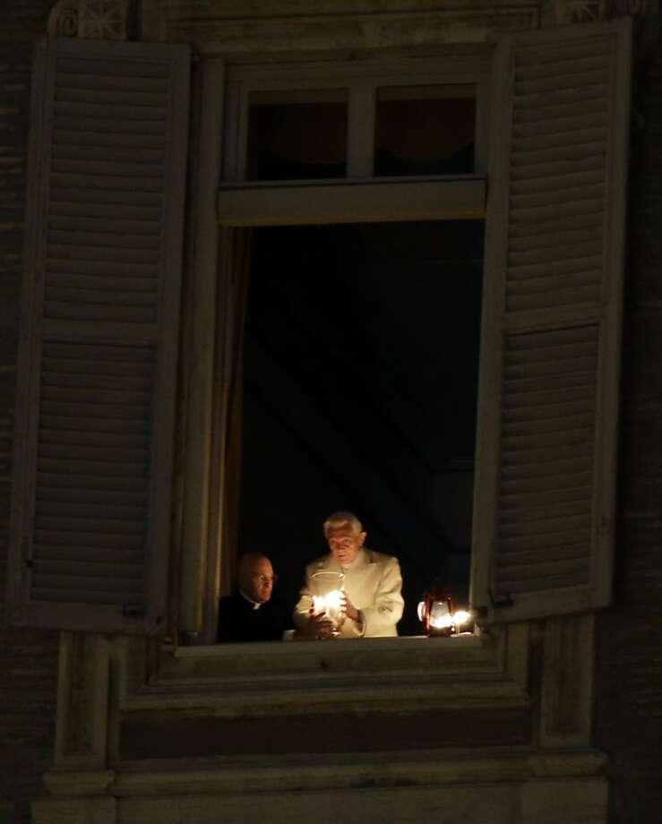 Pope Benedict XVI lights a candle at his studio window overlooking St. Peter's Square at the Vatican, after the unveiling of the Nativity scene, Monday, Dec. 24, 2012. Pope Benedict XVI has lit a Christmas peace candle set on the windowsill of his private studio overlooking square. Pilgrims, tourists and Romans gathered below in St. Peter's Square for the inauguration Monday evening of a Nativity scene and cheered when the flame was lit. Later, he will appear in St. Peter's Basilica to lead Christmas Eve Mass. Photo: Gregorio Borgia, Associated Press