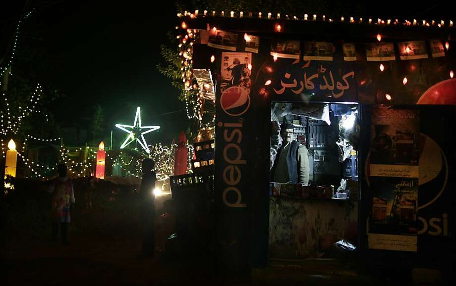 A Pakistani man, right, stands inside his grocery story which id decorated with festive lights, for the Christmas holiday in a Christian neighborhood in Islamabad, Pakistan, Monday, Dec. 24, 2012. Photo: Muhammed Muheisen, Associated Press