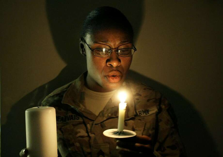 A U.S. army woman with the NATO- led International Security Assistance Force (ISAF) blows a lit candle on Christmas eve at the U.S.-led coalition base in Kabul, Afghanistan, Monday, Dec. 24, 2014. Photo: Musadeq Sadeq, Associated Press